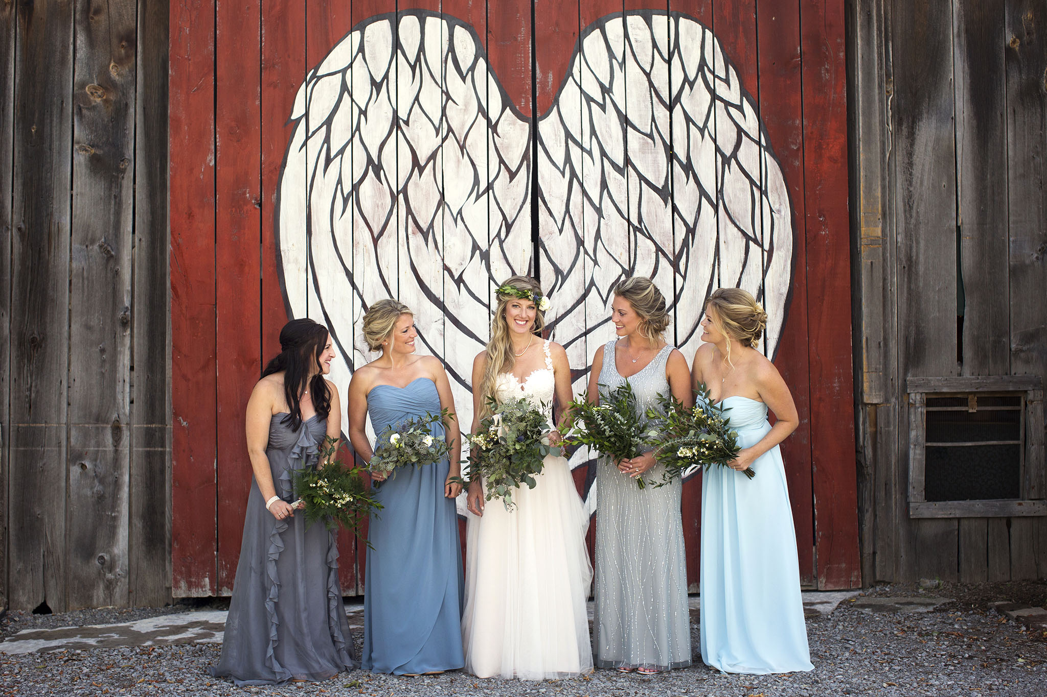 One bride with 4 bridesmaids , all holding flowers beneath the wings at Century Barn.
