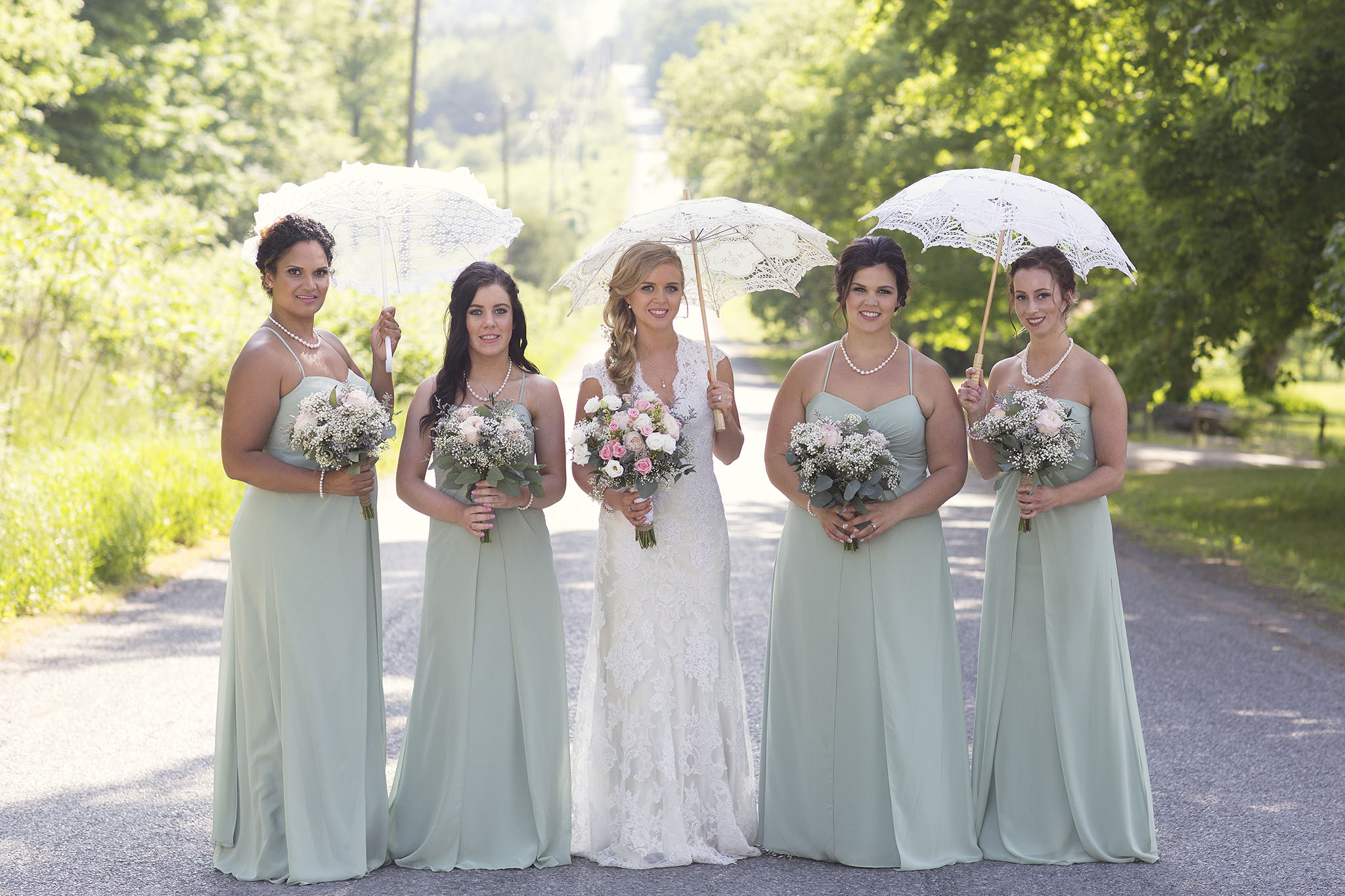 Formal sun umbrella bridal party picture.