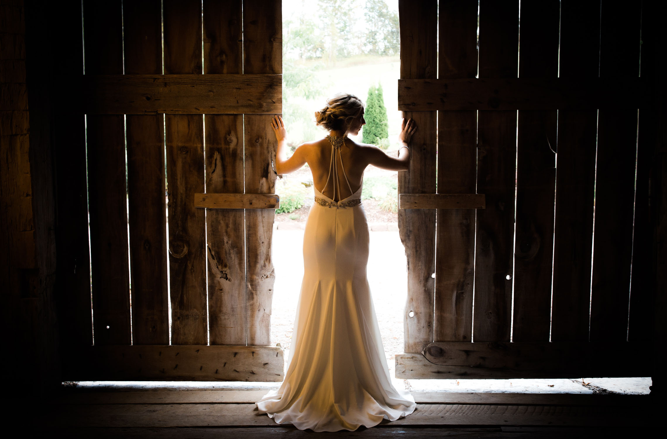 Gorgeous shot of bride with sunlight streaming thru the gaps of the old barn.