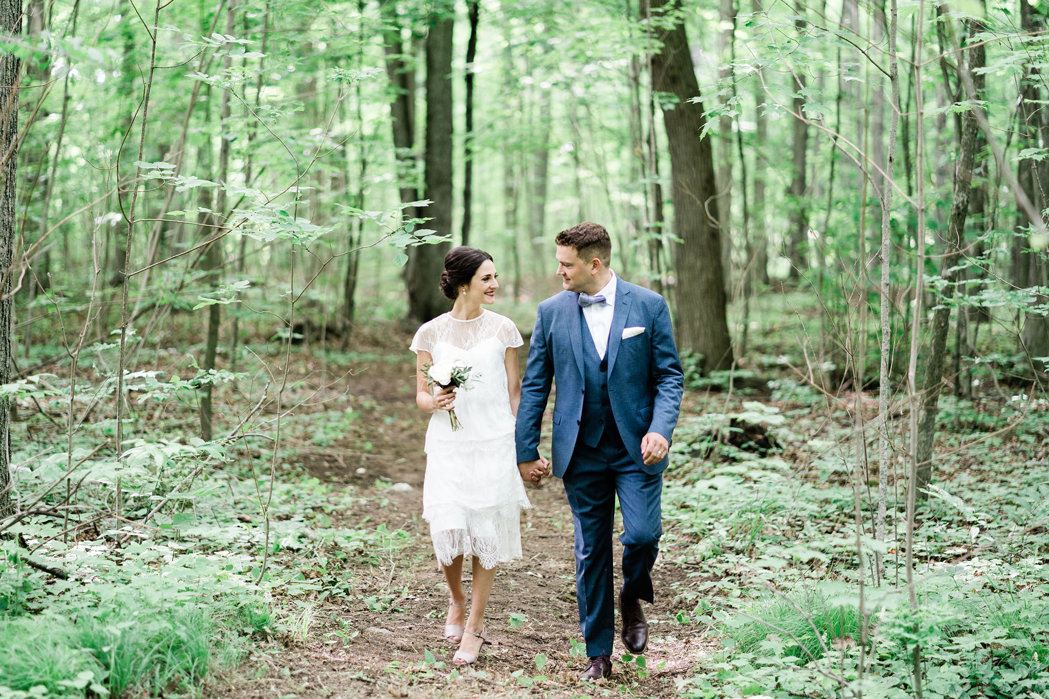 Happily married couple waking thru a quiet and peaceful forest hand in hand, just after getting married. Bride wearing cocktail length dress reminiscent of a 1930's flapper. Gentleman wearing dark blue suit with bowtie. Floral arrangement is small, delicate and classic.