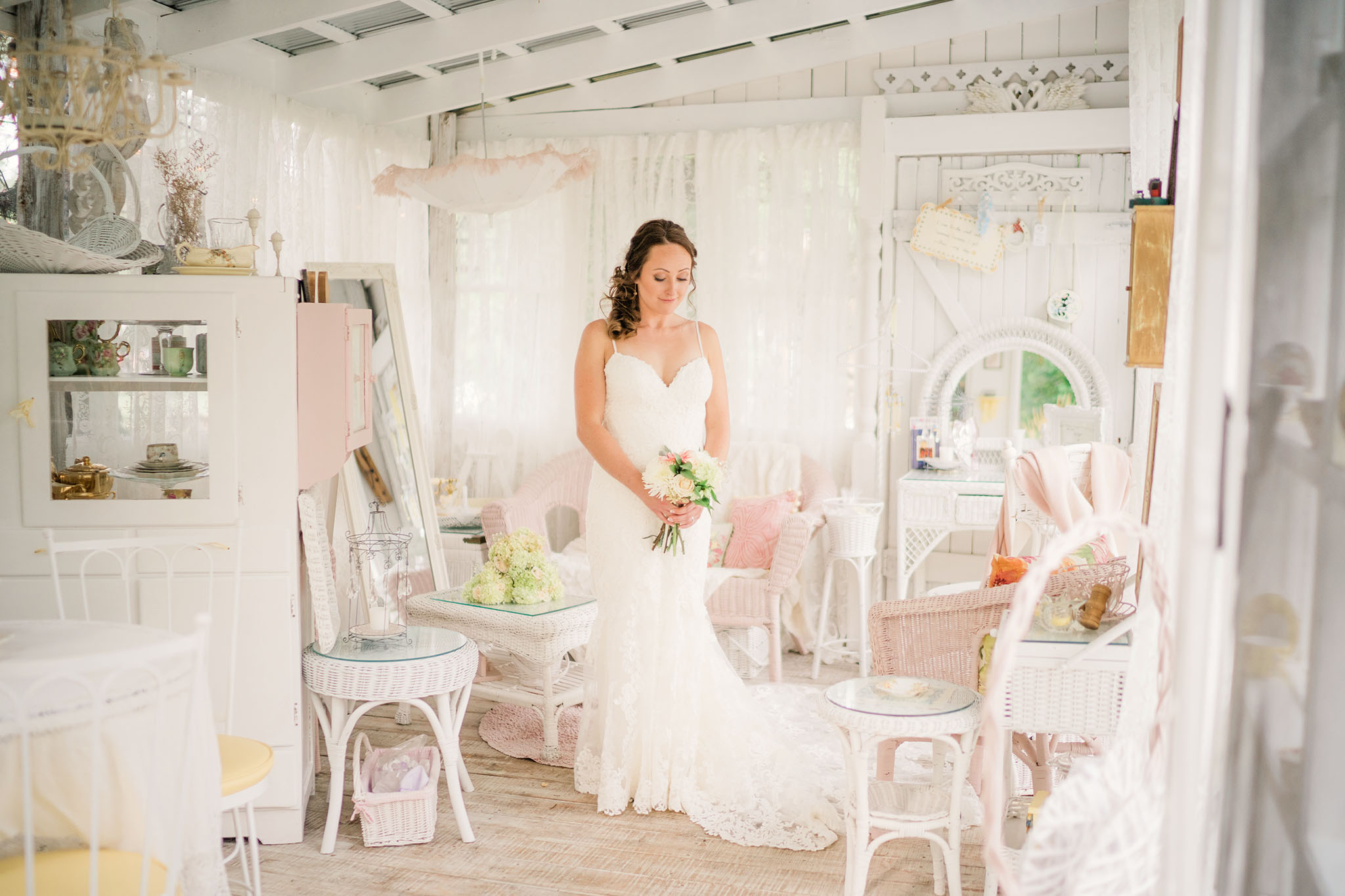 Bride in white dress standing in centre of room contemplating her big moment that is about to happen.