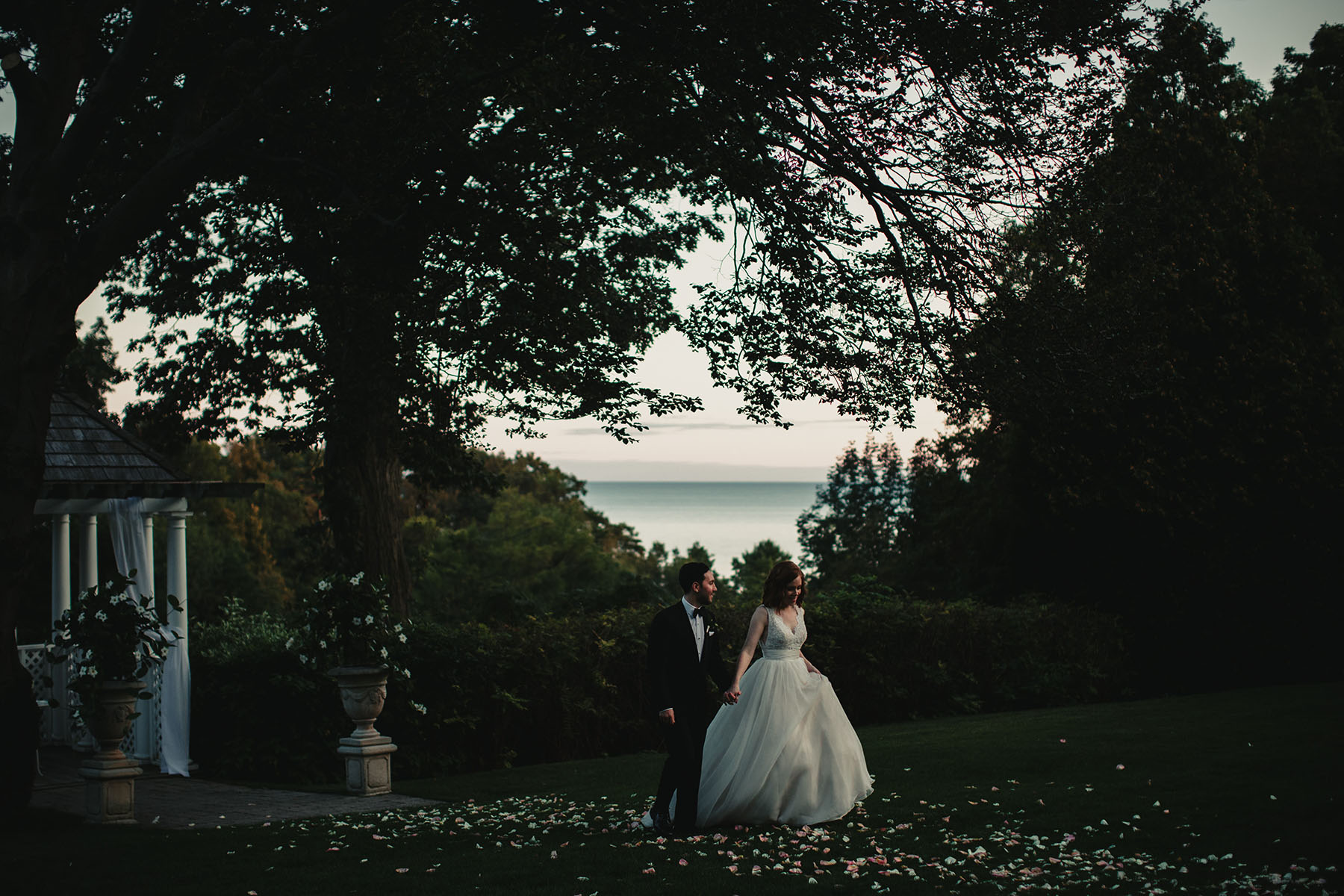 Beautiful setting of golf course over looking Lake Ontario. Bride and groom walking thru the grass.
