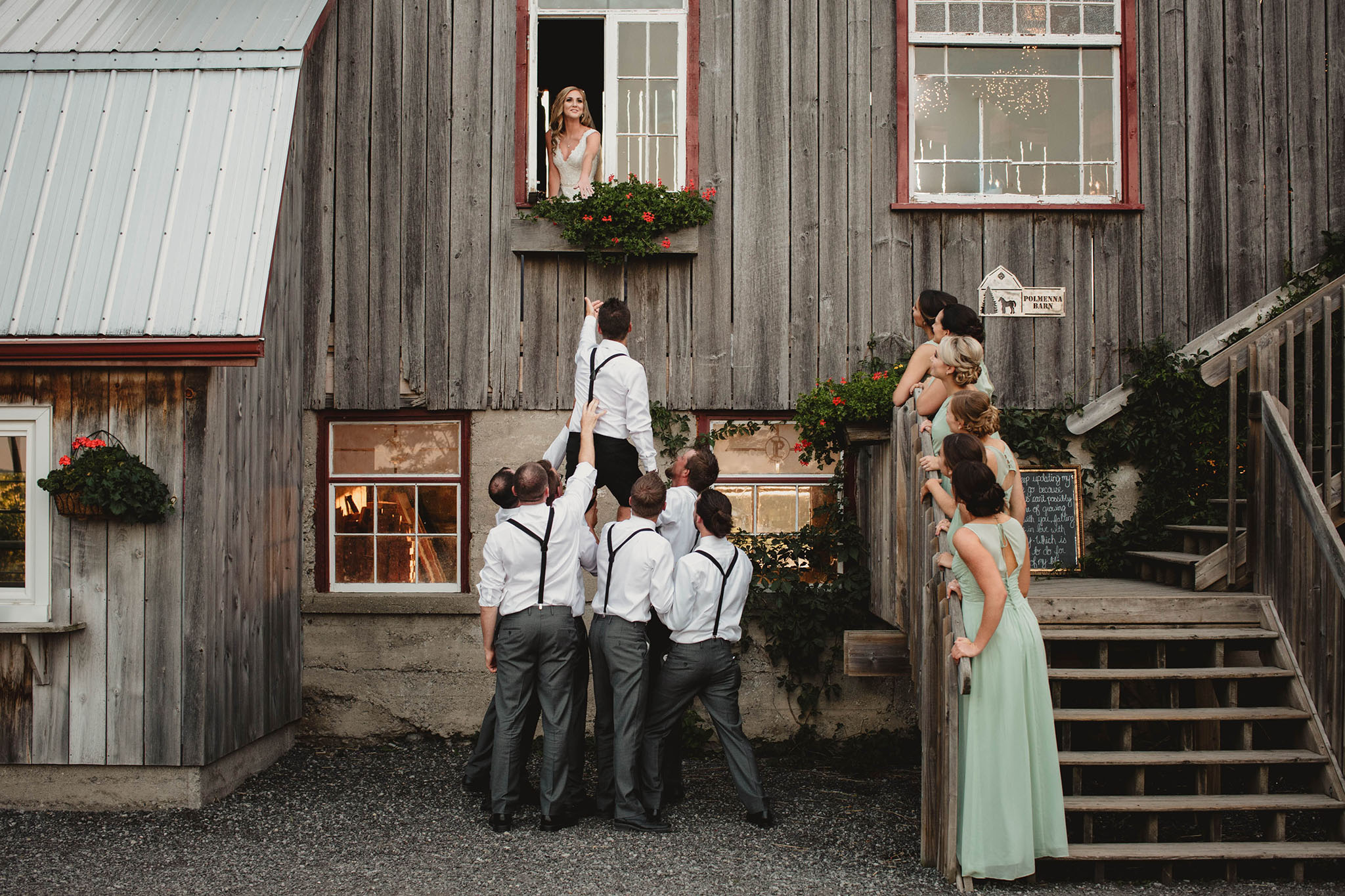 Bride looking out Barn window and below are the groom with the groomsmen lifting him up to the window.