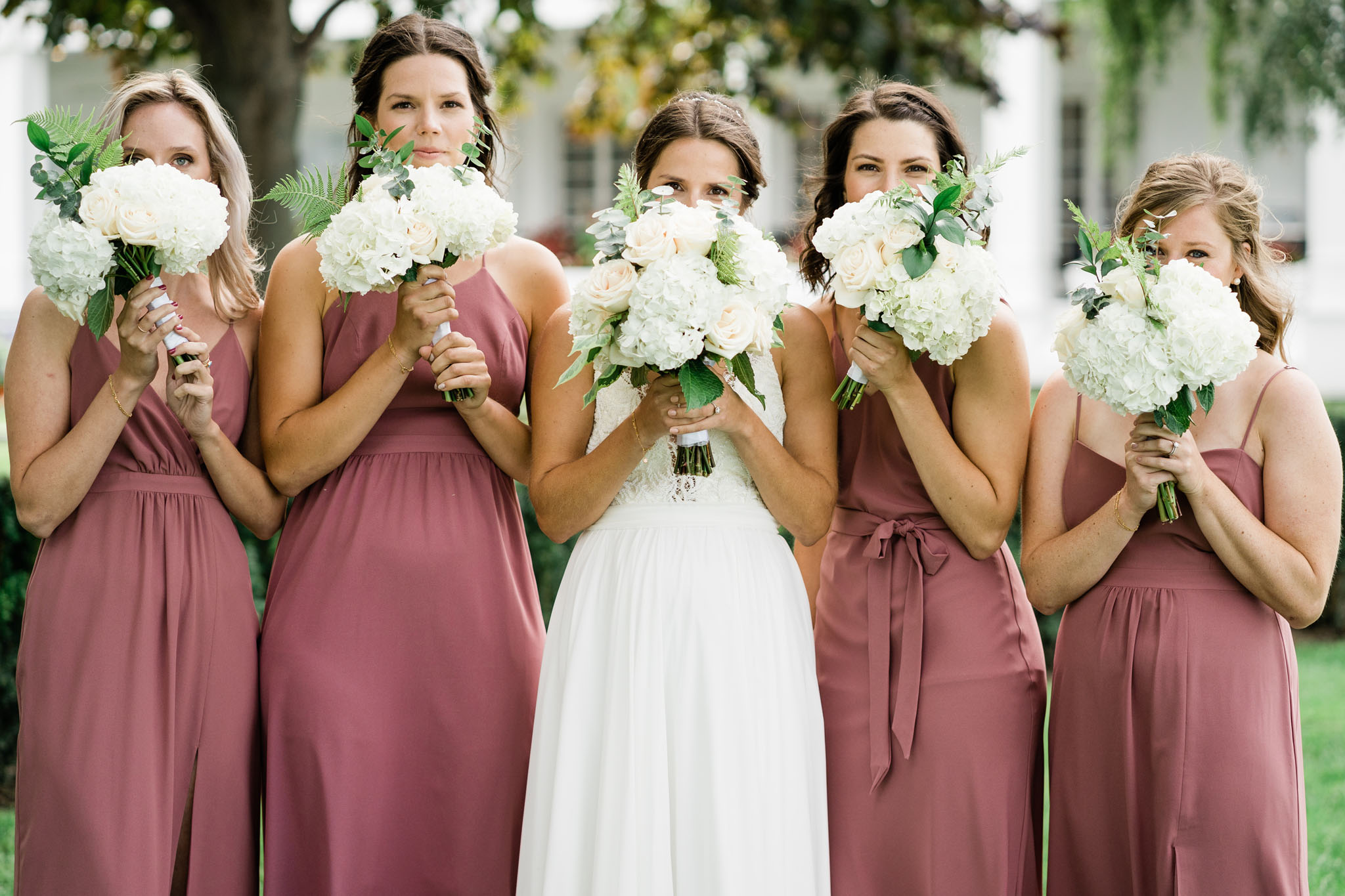 Bridesmaids all peaking out from behind their flowers.