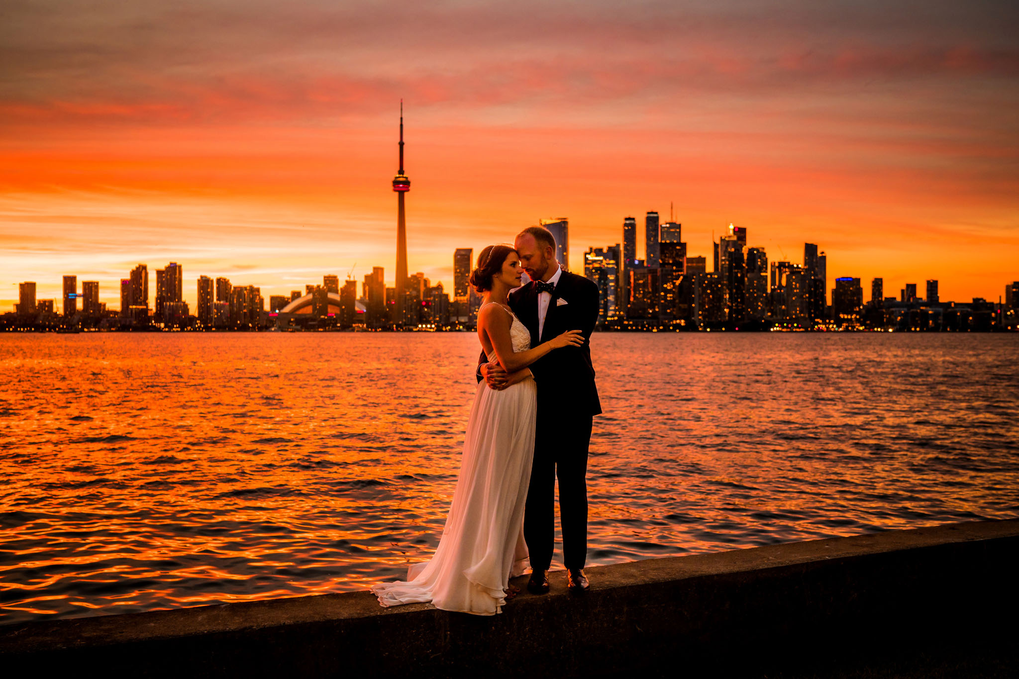 Sunset at the Royal Canadian Yacht Club. Gorgeous couple with red orange background. This one is definitely going in a frame!