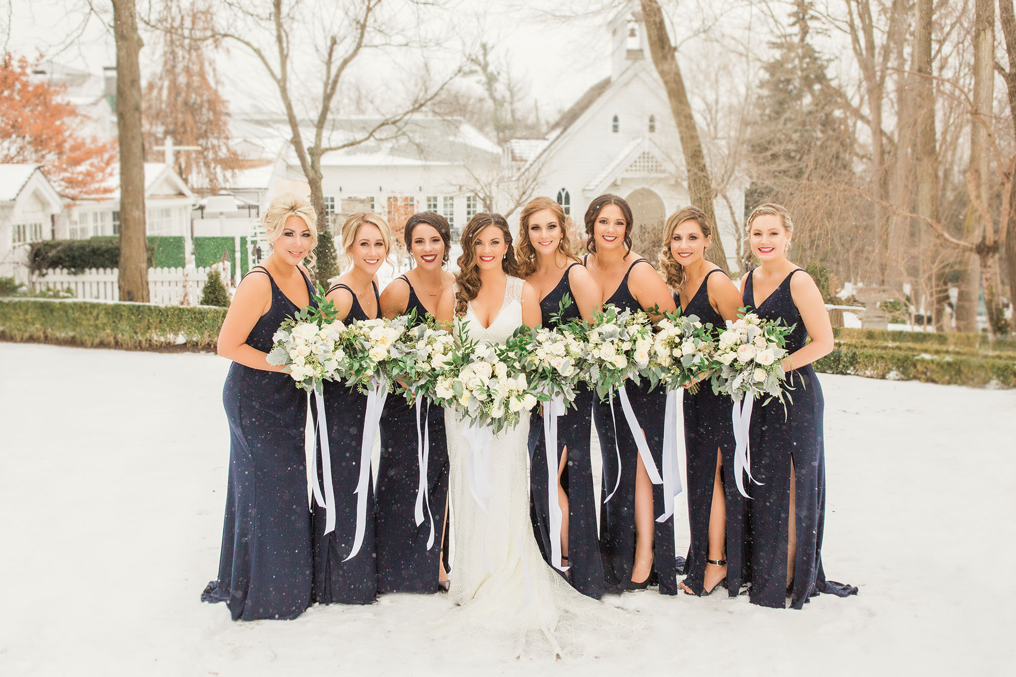 Eight beautiful ladies all outside with snow all around. Standing in front of heritage house with green hedges and gorgeous white floral bouquets.